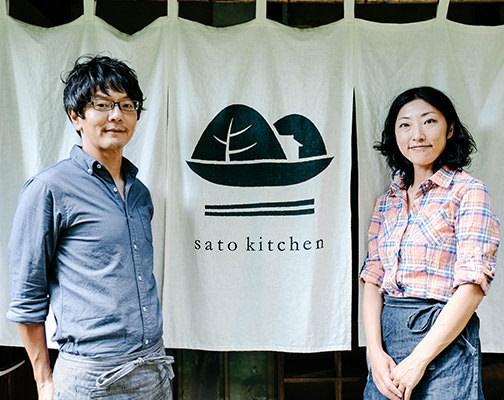 店の入り口に立つ夫婦の写真